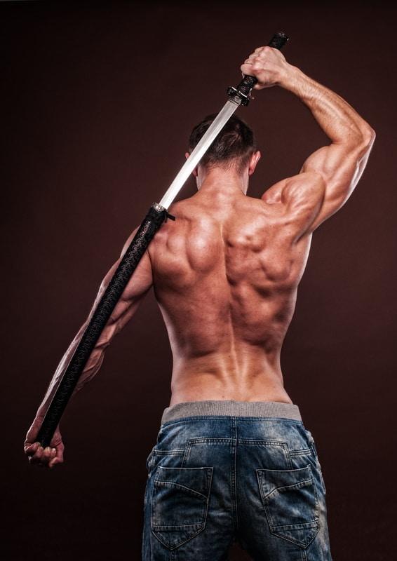 shirtless young man posing with katana sword