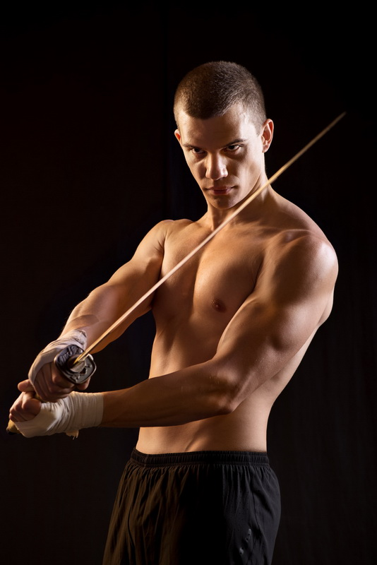 Young Man Holding Samurai Sword on Black Background.