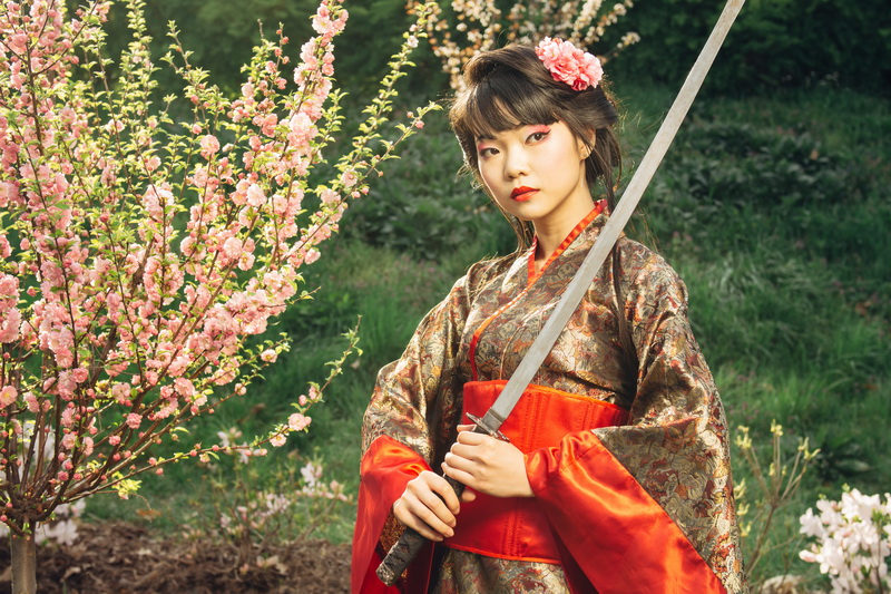 Korean woman or geisha in kimono holding samurai sword near face